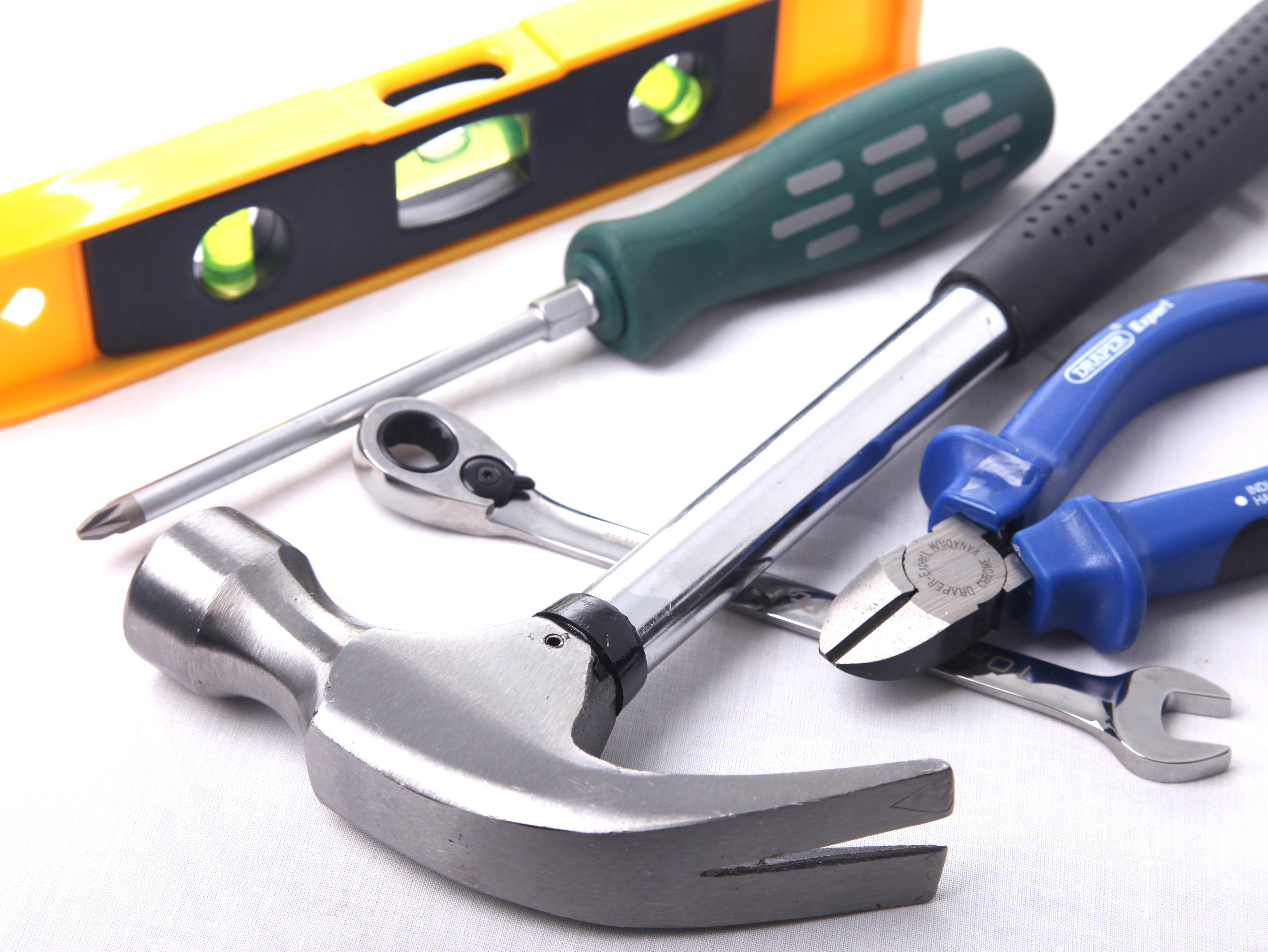 Assorted tools: hammer, screwdriver, torpedo level, wrench, wire cutter.