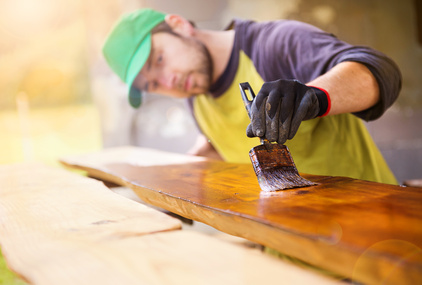 A man varnishing a plank with a brush