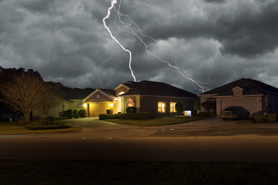 A home with power from a generator in a dark neighborhood power outage. Lightning flashes behind the house.