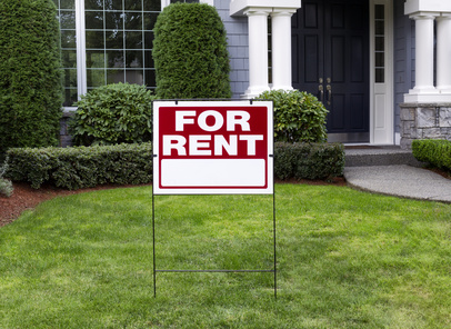 A house with a 'for rent' sign in the front lawn.